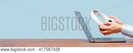 Laptop And Hands With Headphones On White Desk