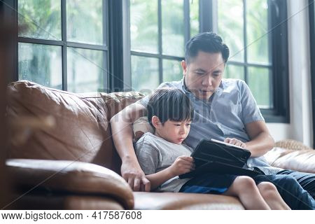 Asian Father Teaching His Young Son For Lesson On E-learning Classes In Tablet At Home. The Boy Usin