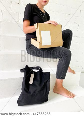 Beautiful Young Woman In Black T-shirt And Jeans With Tote Bag And Cardboard Box