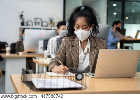 Asian Young Businesswoman Working On Computer In Office With New Normal Lifestyle Concept. Man And W