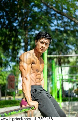 A Naked Asian Muscular Man In A Sitting Pose And Showing His Muscular Arms