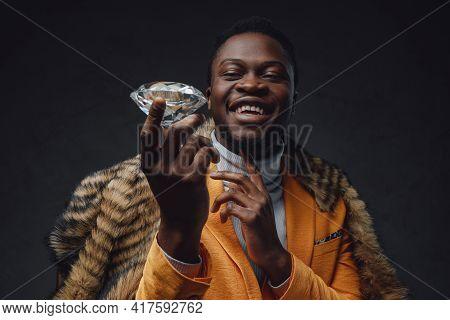 Happy Black Man In Yellow Coat Holding Diamond