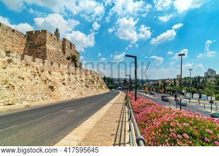 View of ancient walls, Tower of David and urban road under beautiful sky in Jerusalem, Israel.