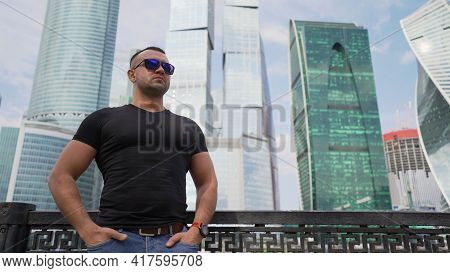 Portrait Of Brutal Man In Sunglasses In The City On The Background Of Large Building. Brutal Guy In