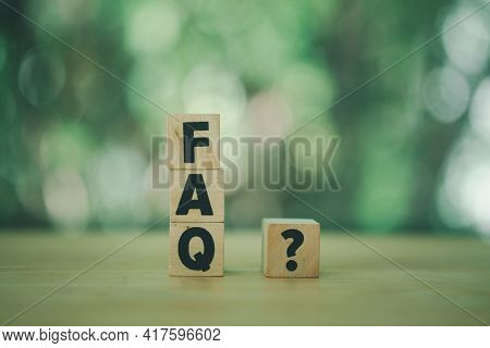 Close-up Shot Of Faq And Question Marks Wooden Blocks. Wood Letters As Faq Abbreviation