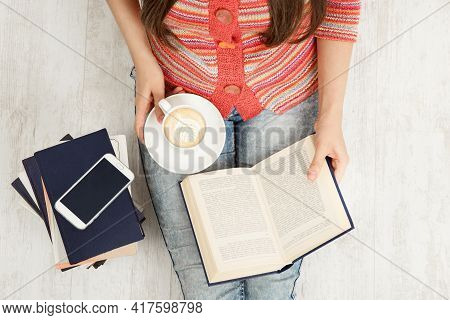Close Up Women Hands Holding Coffee Cup And Reading Opened Book. Top View Of Woman With Teacup Havin