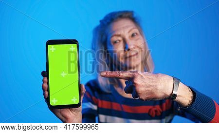 Elderly Woman Holding Smartphone With Vertical Green Screen And Pointing Finger At It With Smile. Hi
