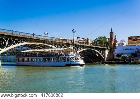 Seville, Andalusia, Spain - May 12, 2013: Tourist Ship Passes Under The Bridge Of Isabel Ii (puente