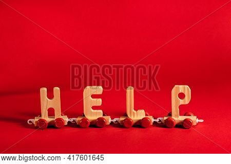 Wooden Train Made Of Letters Help On Red Backdrop. Humanitarian Aid, Shipping, Material Assistance,
