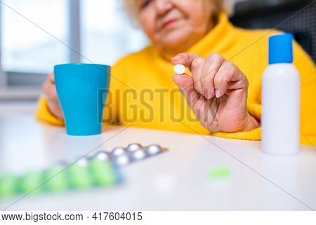 Ill Old Woman Taking A Pill From A Pill Dispenser In Her House
