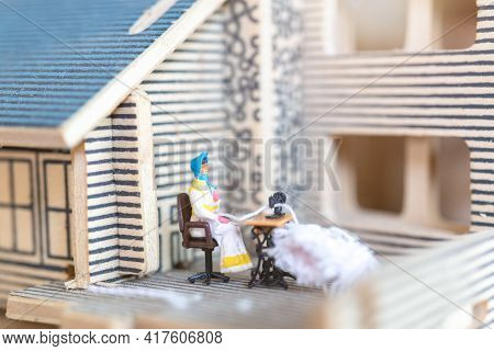 Miniature People Woman Sewing On A Sewing Machine At Her Home