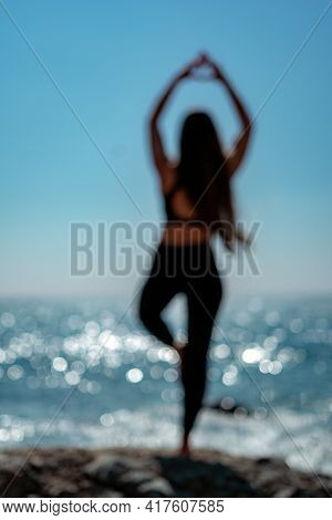 Abstract Defocused Silhouette Of Young Woman With Long Hair, Fitness Instructor In Leggings And Tops