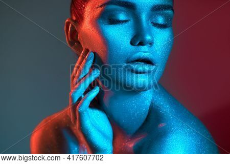 Fashion model woman in colorful bright sparkles and neon lights posing in studio, on black, portrait of beautiful sexy girl, trendy glowing sequins make-up. Art design make up. Glitter Vivid makeup.