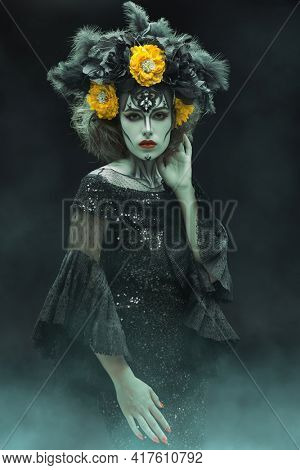 Portrait of a beautiful and scary Calavera Catrina over dark smoky background. Sugar skull makeup and dress. Dia de los muertos. Day of The Dead. Halloween.