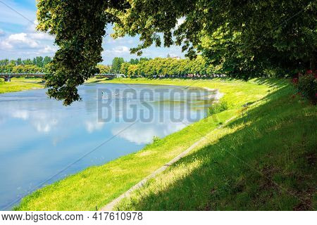 Embankment Of The River Uzh. Wonderful Urban Scenery In Summer. View From Beneath The Shadow Of A Li