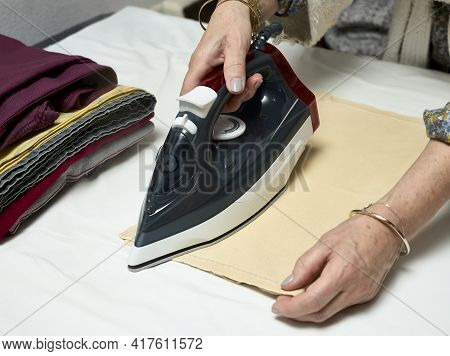 Woman\'s Hands With An Iron Ironing Clothes
