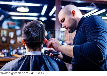 Hairstylist Cutting Hair Of Male Customer At Barber Shop