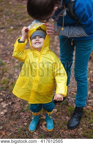 Mom And Child Walk In The Forest After The Rain In Raincoats Together, Mom Puts On A Raincoat