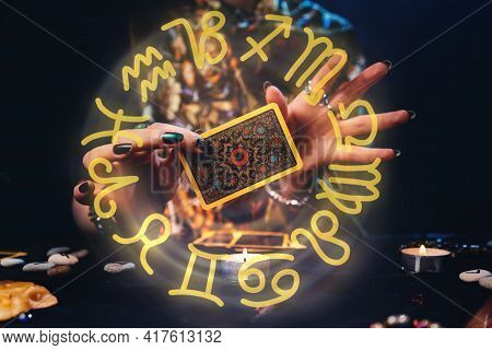 Witches Hands Holding A Tarot Card. The Zodiac Circle Surrounds The Hand. Concept Of Astrology And E