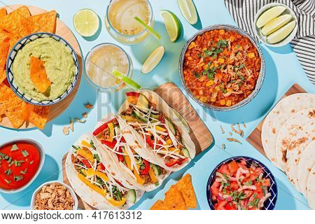 Mexican Food Table With Traditional Dishes. Chili Con Carne, Tacos, Tomato Salsa, Corn Chips With Gu