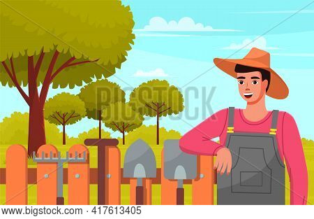 Male Gardener In Summer Garden Landscape With Green Trees Wood Fence And Garden Tools Against Forest
