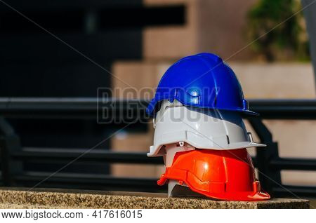 Safety First. White, Orange And Blue Safety Helmet Stacked In Construction Site Building, Safety Equ