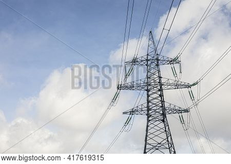 High Voltage Transmission Line Against The Sky. White Cumulus Clouds. Power Supply Of A City.
