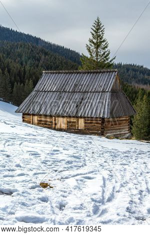 Typical Traditional Highlander Cottage. Wooden Shepherd's Hut.  Mountain Glade In Winter Scenery. Ta