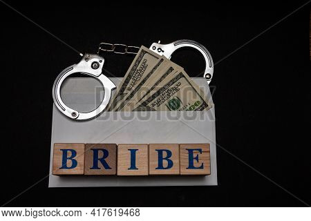 Handcuffs On An Envelope With Dollars On A Black Background And The Inscription Bribe From Wooden Cu