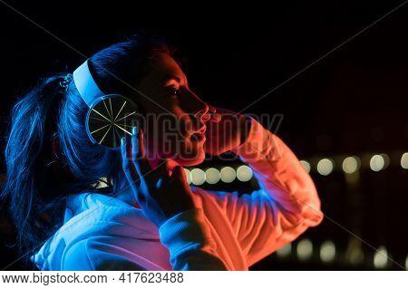 Millennial Girl Enjoying Nightlife In City Street. Listening Music With Headphones. Gorgeous Hipster
