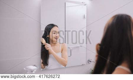 Beautiful Young Woman In White Undershirt Is Combing Her Hair And Smiling While Looking Into The Mir