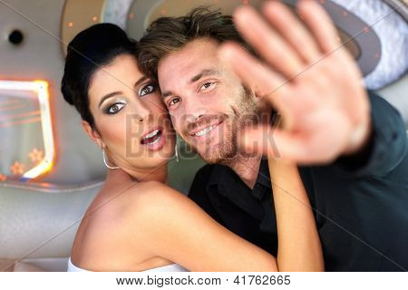Celebrity couple hugging in limousine, trying to avoid photographing.
