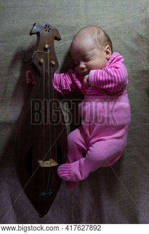 A Newborn Baby In Pink Clothes Sleeps In An Embrace With A Wooden Old Folk Stringed Musical Instrume