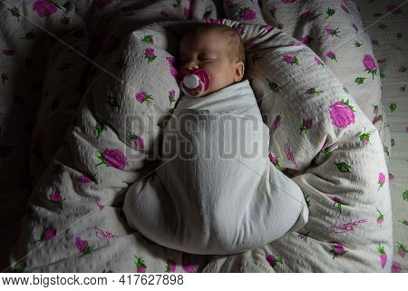 A Newborn Baby, Swaddled In A White Diaper In A Fetal Position, Sleeps In A Rolled-up Nest Blanket I