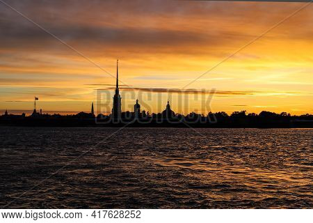 Sunset Over The City On The Coast. Beautiful Orange Sunset Over The River, The Silhouette Of The Cit