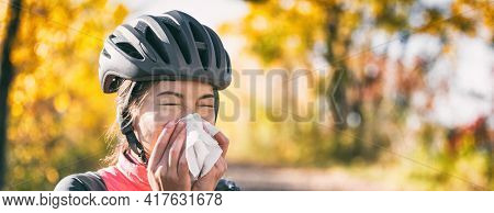 Cough in tissue covering nose and mouth when coughing outside as COVID-19 hygiene guidelines for Coronavirus spread prevention. Biking cyclist girl sneezing in paper outside. Panoramic banner.