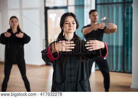 Composed Qigong Coach Doing Embrace Gesture With Arms