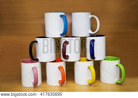 Ceramic White Mugs With Beautiful Handles Of Orange Green Blue Yellow Purple Colors Arranged In A Py