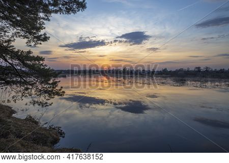 Sunset River Quiet Landscape View. Evening By The River. Pine Branches Against The Background Of The