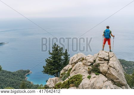 Young Hiker Backpacker Man Using Trekking Poles Enjoying The Mediterranean Sea On Clifftop During Ly