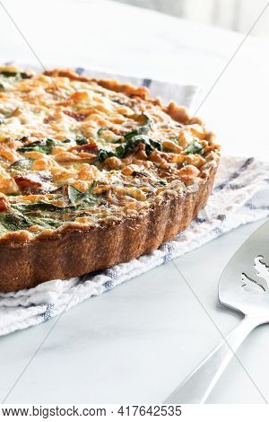 Freshly Baked Spinach And Bacon Quiche Cooling On A Kitchen Towel Against A Sunny Window.