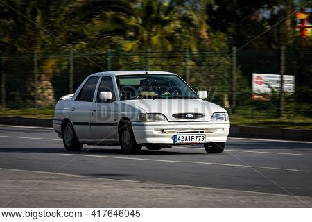Antalya, Turkey - April 12 2021:   White Ford Escort 1992   Is Driving Fast On The Street On A Warm