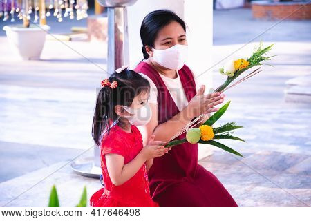 Family Wearing Mask Is Going To Pay Homage To Monks At Temple. Mother And Daughter Hands Holding Flo