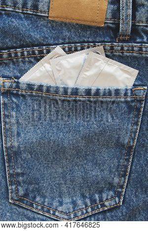 Three Condoms In The Back Pocket Of Blue Jeans, Contraception And Safe Sex Concept Vertical Photo