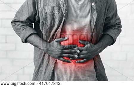 Unrecognizable African Man Having Stomachache Touching Abdomen On Gray Wall