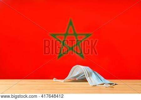 A Medical Mask Lies On The Table Against The Background Of The Flag Of Morocco. The Concept Of A Man