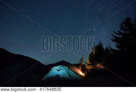 Beautiful View Of Night Starry Sky Over Grassy Hill With Tourist Tents And Trees. Mountain Valley Wi