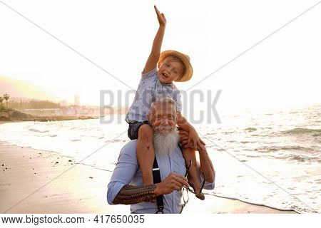 Little Boy And Senior Man Celebrating Grandfather's Day Together, Smiling, Having Fun On The Beach.