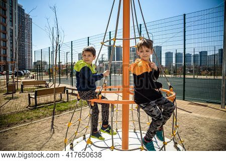 Two Young Boy Active Little Child Playing Climbing At Spring Metal Playground His Hand To Exercise A