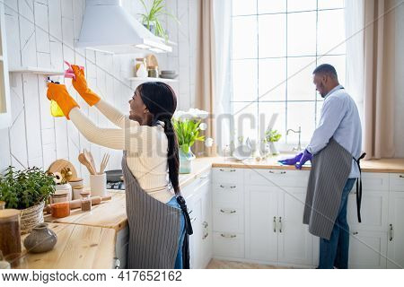 Millennial Black Couple Cleaning Their Kitchen Together, Enjoying Household Duties, Free Space. Hous